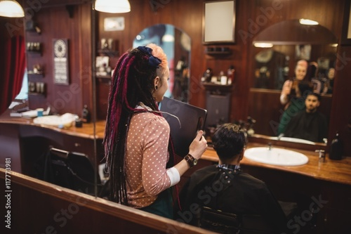 Female barber showing man his haircut in mirror