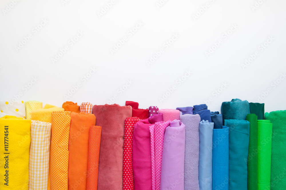 Fototapety, obrazy: Rolls of bright colored fabric on a white background.