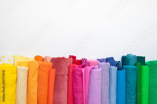 Photo Rolls of bright colored fabric on a white background.