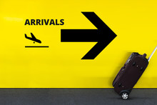 Airport Sign With Airplane Arrival Icon On The Yellow Wall. Passenger Rolling The Luggage In Motion
