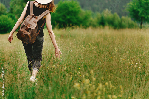 Foto  stylish hipster woman walking in grass and holding  in hand herb