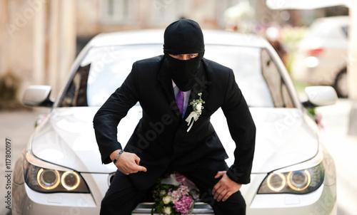 Fotografie, Obraz  Groom in black mask sits on the grey BMW
