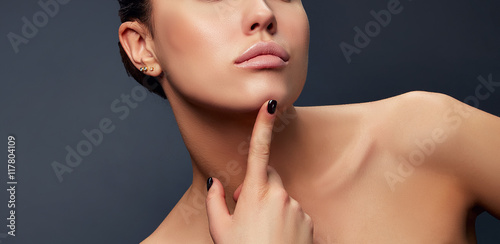 Fotografie, Obraz  Close-up lips, neck and shoulder of young girl, touching her chic over grey back