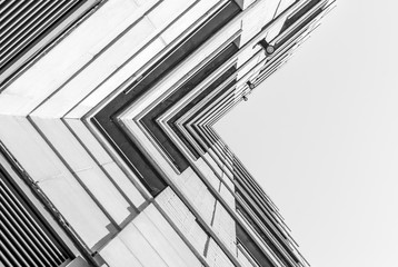 Fototapeta Urban Geometry, looking up to building. Modern architecture black and white, concrete and glass. Abstract architectural design. Inspirational. Artistic image and point of view.