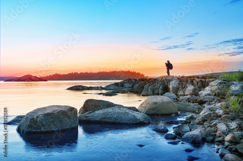 Silhouette of tourist with camera on rocks mysterious island