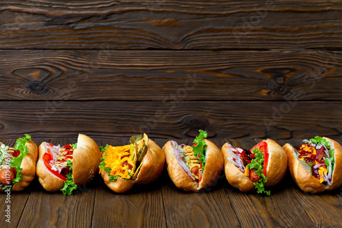 Fotomural lot of big delicious hot dogs with sauce and vegetables on wooden background