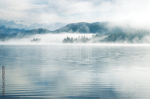 Heavy fog in the early morning on a mountain lake Early morning on Yazevoe lake in Altai mountains, Kazakhstan