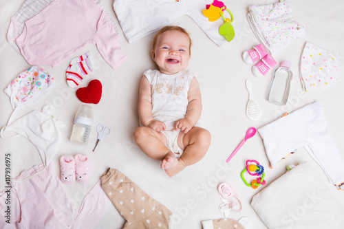 Fotografia  Baby on white background with clothing, toiletries, toys and health care accessories