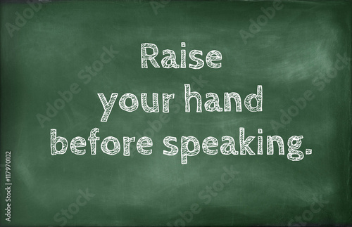 Fotografie, Obraz  Raise your hand before speaking,school rules written on a chalkboard