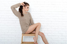 Woman Sitting On The Wooden Chair. Photo In Front Of White Brick Wall.