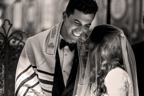 Fototapeta Jewish wedding. Smiling groom bends to the bride obraz
