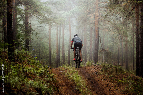 Foto  male athlete mountainbiker rides a bicycle along a forest trail