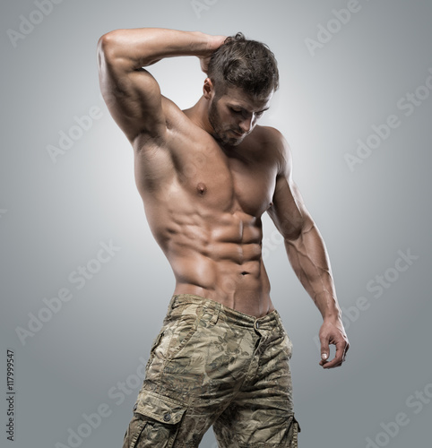Fotografie, Obraz  Muscular athlete bodybuilder man on a gray background