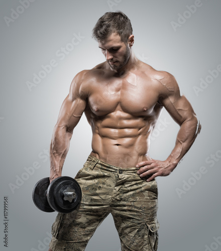Fototapeta Muscular athlete bodybuilder man on a gray background