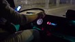 Bus driver behind the steering wheel riding intercity coach on a city street at night using smart phone