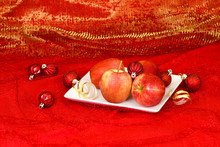 Plate Of Red Apples By Holiday Ornaments And Ribbon