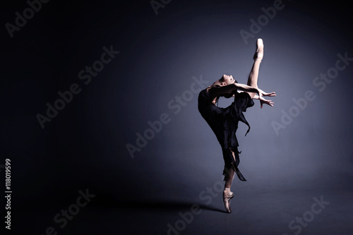 Junge Ballerina in einem schwarzen Anzug tanzt in ein dunkles Studio Fototapete