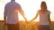 Man and woman holding hands wheat field into the beautiful sunset.