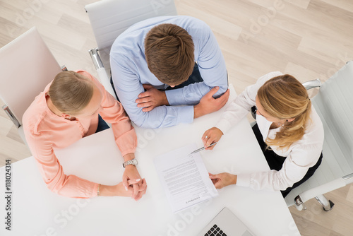 Estate Agent Explaining Document To Young Couple