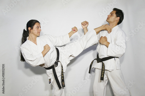 Poster Vechtsport Karate master girl with white kimono black belt does high side kick, kikome geri to the neck of black belt man
