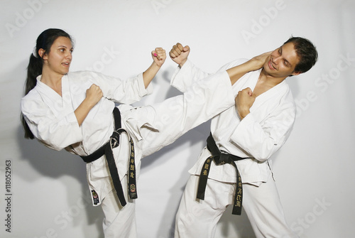 Deurstickers Vechtsport Karate master girl with white kimono black belt does high roundhouse kick, mavashi geri, to the head of black belt karate man