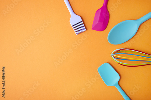 Colorful kitchen utensils arranged on an orange background ...