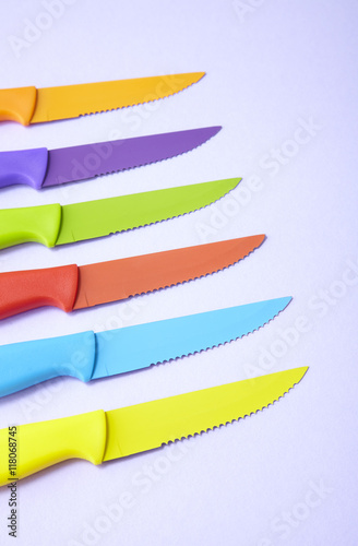 Colorful kitchen knives arranged on a purple background ...
