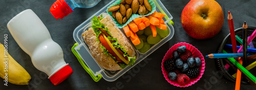 Fotografía  School lunch box with books and pencils in front of black board