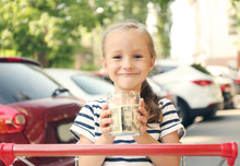 Cute Girl Holding Bank With Money In Hands And Sitting In Shopping Cart, Outdoors