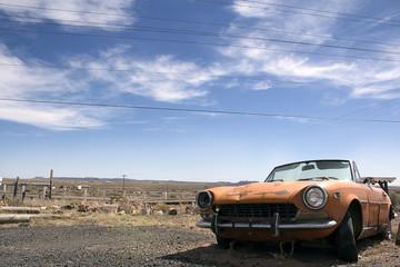 OLD RUSTY CAR IN DESERT