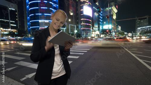 Obraz na płótnie Młoda kobieta za pomocą panelu dotykowego na ruchliwej ulicy miasta Seul nocy w Republice Korei. Oświetlone budynki, autostrada z ruchem samochodowym i przejście dla pieszych w tle