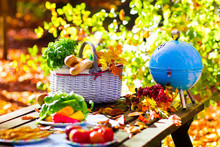 Grill And Picnic Basket In Autumn Garden