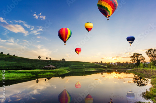 Recess Fitting Balloon Colorful hot-air balloons flying over tea plantation landscape at sunset.