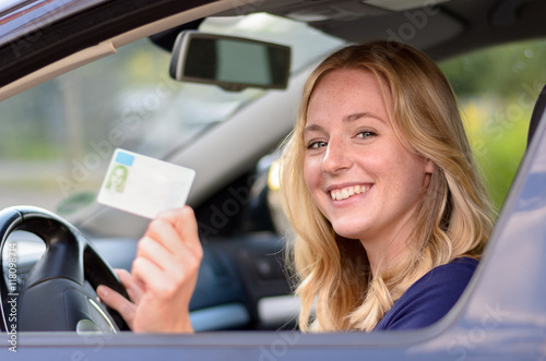 Photo Happy young woman showing off her drivers license