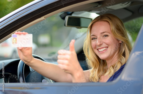 Young blond woman showing off her drivers license Canvas Print