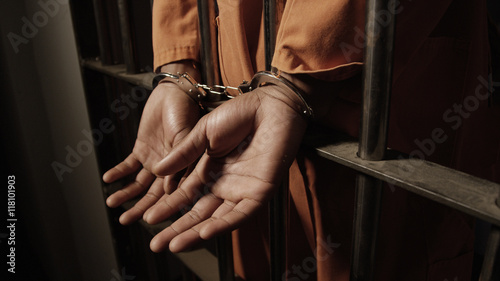 Valokuva  African man in prison - hand cuffed through the bars of his jail cell