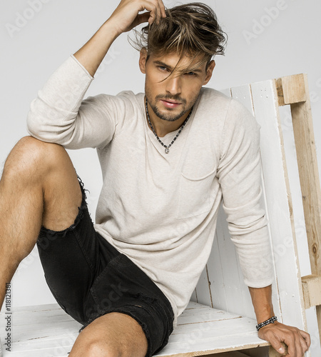 Portrait of handsome man with hand in his hair and sitting on pa Fototapet