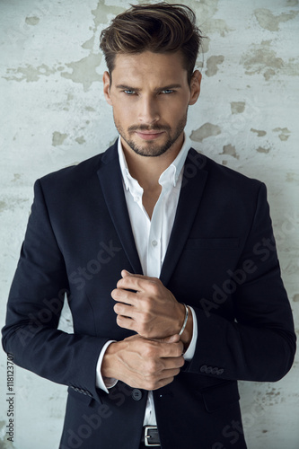 Stampa su Tela  Portrait of sexy man in black suit