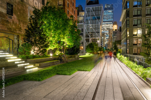 Photo  The High Line promenade illuminated at twilight surrounded by modern and older buildings in Chelsea