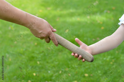 woman giving the relay baton to the next generation into a child's hand Canvas Print