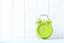 Green Alarm Clock On Blue Wooden Table