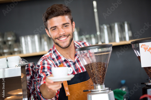 Fotografie, Obraz  Smiling waiter offering cup of coffee