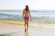 beautiful girl walking the summer beach
