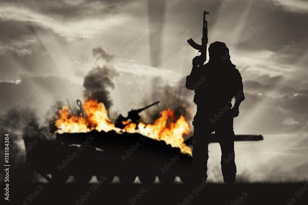 Fototapeta Silhouette of terrorist holding rifle against burning tank