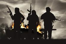 Silhouette Of Terrorist Holding Rifle Against Burning Tank