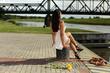 Piękna kobieta siedzi tyłem na brzegu rzeki.