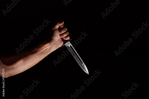Fotografie, Obraz  Man's hand with a knife in the dark