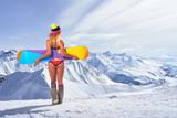 Back view of girl in bikini holding snowboard above head