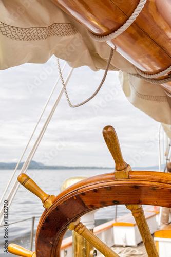 Wooden wheel on a big sailboat at sea. Close up nautical detail © Crin