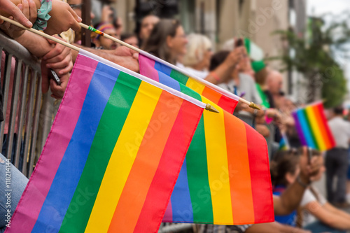 Fotografía  Gay rainbow flags at Montreal gay pride parade with blurred spectators in backgr